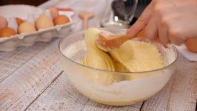 Το χέρι γυναικών αναμιγνύει τα sponge-cake συστατικά σε ένα κύπελλο γυαλιού με ένα ξύλινο κουτάλι φιλμ μικρού μήκους