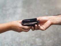 Το χέρι γυναικών δίνει το πορτοφόλι στον άνδρα Χρήματα & οικονομικός ομο στοκ εικόνες
