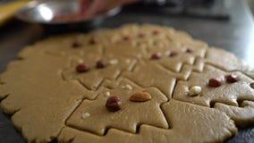 Το χέρι γυναικών διακοσμεί τα ακατέργαστα μπισκότα που κόβονται με μορφή χριστουγεννιάτικου δέντρου με την κινηματογράφηση σε πρώ απόθεμα βίντεο