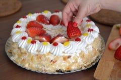 Το χέρι γυναικών διακοσμεί ένα κέικ κρέμας με τις φράουλες Στοκ Εικόνες