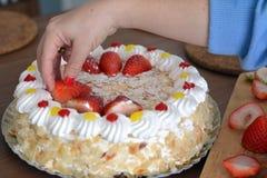 Το χέρι γυναικών διακοσμεί ένα κέικ κρέμας με τις φράουλες Στοκ φωτογραφίες με δικαίωμα ελεύθερης χρήσης