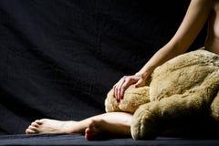 Το χέρι γυναικών και το πόδι και μέρος ενός μεγάλου παιχνιδιού αντέχουν Στοκ Εικόνες