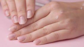 Το χέρι γυναικών κινηματογραφήσεων σε πρώτο πλάνο στο ροζ κάνει το μανικιούρ για την απόθεμα βίντεο