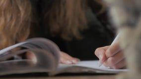 Το χέρι γυναικών κρατά ένα βιβλίο και κινεί τα δάχτυλά της κατά μήκος της σελίδας διαβάζοντας το έγγραφο ανάγνωσης ελεύθερου χρόν απόθεμα βίντεο