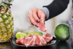 Το χέρι γυναικών κρατά το κόκκινο ξεφλουδισμένο γκρέιπφρουτ στο πιάτο στοκ εικόνα με δικαίωμα ελεύθερης χρήσης