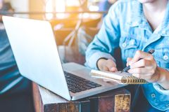 Το χέρι γυναικών λειτουργεί σε έναν φορητό προσωπικό υπολογιστή και γράφει σε ένα notepa Στοκ φωτογραφία με δικαίωμα ελεύθερης χρήσης