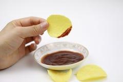 Το χέρι γυναικών με τα τσιπ πατατών βύθισε στο κέτσαπ ντοματών στη διατροφή τσιπ πιάτων και πατατών, πάχυνση στοκ εικόνες με δικαίωμα ελεύθερης χρήσης