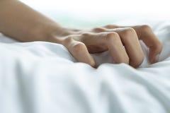 Το χέρι γυναικών με τη χειρονομία οργασμού φύλων θέτει να ενεργήσει στο άσπρο κρεβάτι, κλείνει επάνω στοκ εικόνα