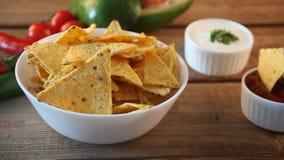 Το χέρι γυναικών παίρνει τα μεξικάνικες nachos και τις εμβυθίσεις τσιπ σε ένα salsa sause φιλμ μικρού μήκους