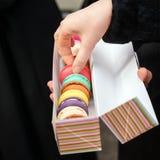 Το χέρι γυναικών παίρνει το κέικ Παραδοσιακά γαλλικά ζωηρόχρωμα macaroons σειρές σε ένα κιβώτιο Στοκ Φωτογραφία