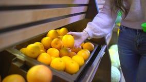 Το χέρι γυναικών που επιλέγει τα λεμόνια στο μανάβικο παίρνει τα λεμόνια στο διάδρομο φρούτων και λαχανικών σε μια υπεραγορά απόθεμα βίντεο