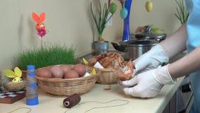 Το χέρι γυναικών προετοιμάζει τα αυγά Πάσχας που βάφονται με την κουζίνα κοχυλιών κρεμμυδιών 4K απόθεμα βίντεο