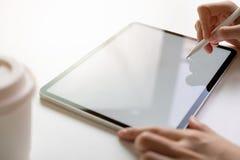 Το χέρι γυναικών χρησιμοποιεί την ταμπλέτα στο γραφείο Πάρτε την οθόνη σας για να βάλετε στη διαφήμιση στοκ εικόνα με δικαίωμα ελεύθερης χρήσης