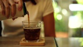 Το χέρι γυναικών χύνει το μη αλκοολούχο ποτό σε ένα ποτήρι του πάγου απόθεμα βίντεο