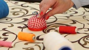 Το χέρι γυναικών ` s παίρνει μια βελόνα από ένα κόκκινο μαξιλάρι κλείστε επάνω απόθεμα βίντεο