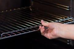 Το χέρι γυναικών ` s ωθεί ή παρεμβάλλει τη σχάρα στο φούρνο στοκ φωτογραφίες