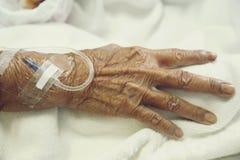 Το χέρι είναι σε μια σταλαγματιά που λαμβάνει μια αλατούχο λύση στοκ εικόνες