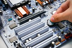 Το χέρι εγκαθιστά την μπαταρία στον υπολογιστή mainboard Στοκ Εικόνες