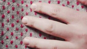 Το χέρι ενός ατόμου αγγίζει ένα γκρίζο πλεκτό μαντίλι με τα κόκκινα σημεία φιλμ μικρού μήκους