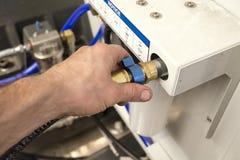 Το χέρι ενός ατόμου σφίγγει το καρύδι ένωσης του υδραυλικού σωλήνα στο τ Στοκ Εικόνα