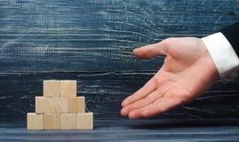 Το χέρι ενός επιχειρηματία δείχνει μια πυραμίδα των ξύλινων τετραγώνων Υποστηρικτής, πώληση και αγορά έννοιας των αγαθών Στοκ φωτογραφία με δικαίωμα ελεύθερης χρήσης