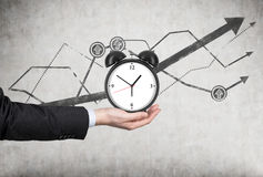 Το χέρι ενός επιχειρηματία κρατά ένα ξυπνητήρι Υπάρχουν διαγράμματα ανάπτυξης γραμμών πίσω από το ξυπνητήρι Μια έννοια της χρονικ στοκ εικόνες