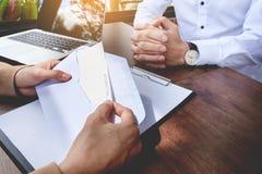 Το χέρι ενός επιχειρηματία παραδίδει ένα γράμμα παραίτησης σε ένα woode Στοκ Φωτογραφίες