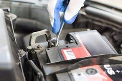 Το χέρι ενός μηχανικού με ένα επίπεδο κλειδί ξεβιδώνει την μπαταρία στο αυτοκίνητο Στοκ Εικόνα