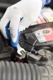 Το χέρι ενός μηχανικού με ένα επίπεδο κλειδί ξεβιδώνει την μπαταρία στο αυτοκίνητο Στοκ φωτογραφία με δικαίωμα ελεύθερης χρήσης