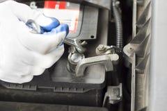 Το χέρι ενός μηχανικού με ένα επίπεδο κλειδί ξεβιδώνει την μπαταρία στο αυτοκίνητο Στοκ Φωτογραφία