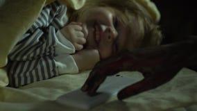 Το χέρι ενός τέρατος ενδιαφέρεται για το τηλέφωνο ενός μικρού κοριτσιού ύπνου απόθεμα βίντεο