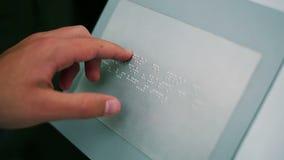 Το χέρι ενός τυφλού ατόμου οδηγεί από τα σύμβολα του αλφάβητου μπράιγ απόθεμα βίντεο