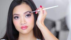 Το χέρι επαγγελματικού πλήρους μοντέρνου φυσικού καλλιτεχνών makeup αποζημιώνει την αρκετά ασιατική γυναίκα χρησιμοποιώντας τη βο απόθεμα βίντεο