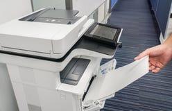 Το χέρι επιχειρηματιών έβαλε το κενό φύλλο εγγράφου στον εκτυπωτή που εισήχθη για την αντιγραφή και την ανίχνευση των εγγράφων Στοκ Εικόνες