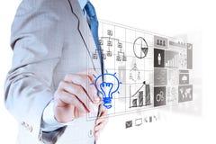 Το χέρι επιχειρηματιών σύρει lightbulb με το νέο υπολογιστή Στοκ Φωτογραφία