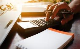 Το χέρι επιχειρηματιών υπολογίζει το κόστος περιόδου με το lap-top για τα στοιχεία αναζήτησης Στοκ φωτογραφία με δικαίωμα ελεύθερης χρήσης