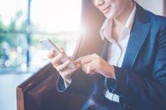Το χέρι επιχειρησιακών γυναικών είναι χρήσεις ένα smartphone στην αρχή στοκ φωτογραφίες με δικαίωμα ελεύθερης χρήσης