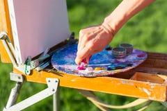 Το χέρι καλλιτεχνών ` s, το οποίο συμπιέζει το ελαιόχρωμα από το σωλήνα μέσα στοκ εικόνες