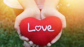 Το χέρι κοριτσιών που κρατά την κόκκινη καρδιά γράφει την αγάπη διατυπώνοντας στην πράσινη χλόη Στοκ Φωτογραφίες