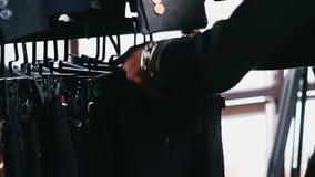 Το χέρι κοριτσιών ` s παίρνει τα ενδύματα στην κινηματογράφηση σε πρώτο πλάνο καταστημάτων απόθεμα βίντεο