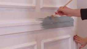Το χέρι κοριτσιών ` s χρωματίζει τον τοίχο με μια βούρτσα απόθεμα βίντεο