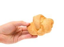 Το χέρι κρατά ριγωτό φρέσκο croissant Στοκ εικόνες με δικαίωμα ελεύθερης χρήσης