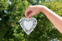 Το χέρι κρατά την κρεμώντας καρδιά φιαγμένη από άσπρο μέταλλο σε ένα πάρκο με το δέντρο Στοκ Φωτογραφίες