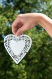 Το χέρι κρατά την κρεμώντας καρδιά φιαγμένη από άσπρο μέταλλο σε ένα πάρκο με το δέντρο Στοκ εικόνα με δικαίωμα ελεύθερης χρήσης