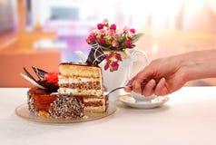 Το χέρι κρατά την ωμοπλάτη με το κέικ κρέμας σοκολάτας κομματιού στην κουζίνα Στοκ φωτογραφία με δικαίωμα ελεύθερης χρήσης