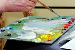 Το χέρι κρατά τη βούρτσα με τα ελαιοχρώματα Στοκ φωτογραφίες με δικαίωμα ελεύθερης χρήσης