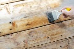 Το χέρι κρατά τη βούρτσα χρωμάτων, που είναι ξύλο λάκκας στοκ φωτογραφία με δικαίωμα ελεύθερης χρήσης