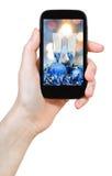 Το χέρι κρατά το κινητό τηλέφωνο με τη ζωή Χριστουγέννων ακόμα Στοκ Εικόνα