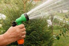 Το χέρι κρατά το χειρωνακτικό ψεκαστήρα για τον κήπο άρδευσης και ποτίσματος με τις προβολές ύδατος στοκ φωτογραφία με δικαίωμα ελεύθερης χρήσης