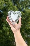 Το χέρι κρατά ψηλά την καρδιά φιαγμένη από άσπρο μέταλλο σε ένα πάρκο μπροστά από το TR Στοκ εικόνες με δικαίωμα ελεύθερης χρήσης